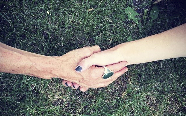 picture of a mom holding her daughter's hand against a grass background. the mom's ring on her index finger is green and the same as the background