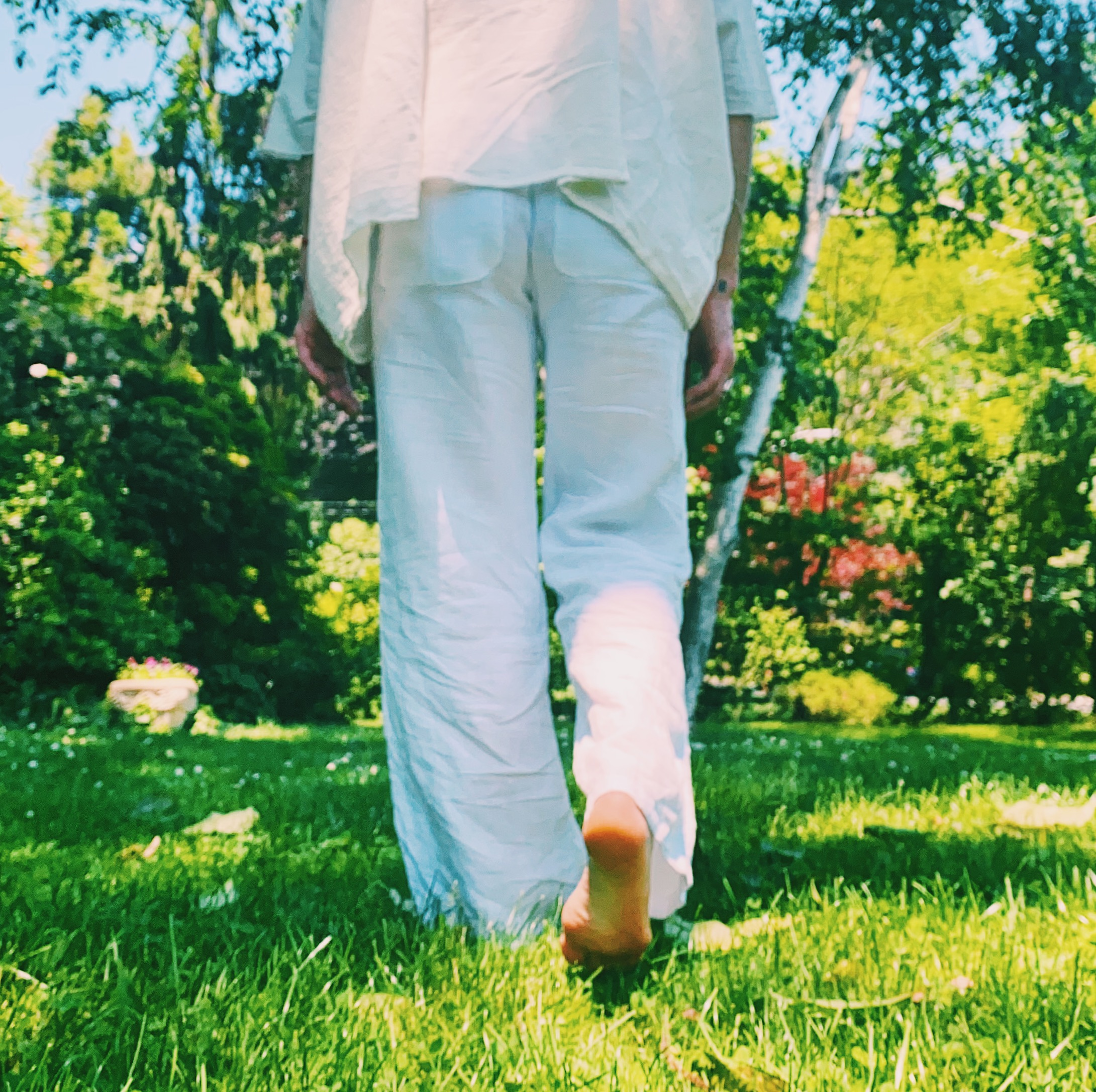 picture of Robin from shoulders down barefoot wearing loose white clothing taking a step in the lush green grass